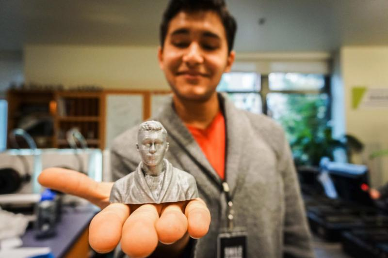 A student holding a 3d printed bust of themself